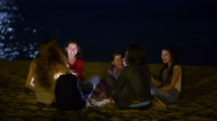 Group o young people spending the night on beach in the moonlight Stock Footage