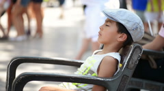 Kid fell asleep outside on bench, people walking around Stock Footage