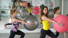 People exercising with fitness ball at gym Stock Footage