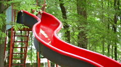 Kid playing in park, on a slide, summer day Stock Footage