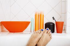 woman legs in bathroom with lot of stylish stuff for care, pedicure creative - stock photo