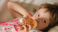 Baby drinking juice form bottle Stock Footage