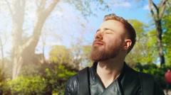 Young, bearded man enjoying sunny weather Stock Footage