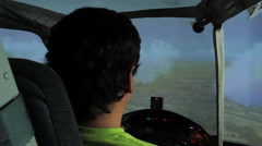 Back view of man training to navigate aircraft in cloudy sky, flight simulator Stock Footage