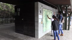 People reading the plaques on the wall at Parque Arvi - stock footage