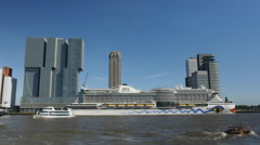 High-rises and cruiseship on river Maas in Rotterdam Stock Footage