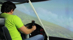 Man enjoying aircraft simulator flight with childlike excitement, entertainment - stock footage