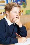 Male Elementary School Pupil Yawning In Classroom Stock Photos