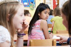 Unhappy Girl Being Gossiped About By School Friends In Classroom - stock photo