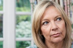 Head And Shoulders Portrait Of Unhappy Mature Woman At Home Stock Photos