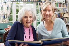 Senior Woman Looks At Photo Album With Mature Female Neighbor Stock Photos