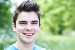 Outdoor Head And Shoulders Portrait Of Smiling Young Man - stock photo