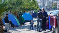 LESVOS, GREECE - OCT 10, 2015: Refugees in the harbor of Mytilene in Lesvos. Stock Photos