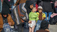 LESVOS, GREECE - OCT 10, 2015: Refugees in the camp. Mom changing boy diapers. Stock Photos