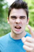 Outdoor Head And Shoulders Portrait Of Angry Young Man - stock photo