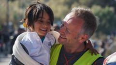 LESVOS, GREECE - NOVEMBER 15, 2015: A refugee child with a volunteer. Emotions Kuvituskuvat