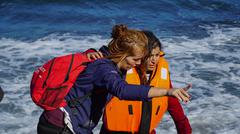 LESVOS, GREECE - OCT 10, 2015: A volunteer helps refugee to get out of the boat. Kuvituskuvat