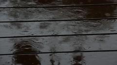 Big raindrops splashing on wooden deck during heavy rain shower Stock Footage
