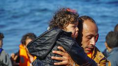 LESVOS, GREECE - NOVEMBER 15, 2015: Children are pulled out of the boat Stock Photos