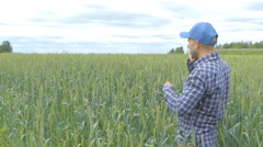 Farmer in a plaid shirt controlled his field.Talking on the phone. - stock footage