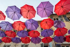 Colorful decorative umbrellas hanging between houses of a street - stock photo