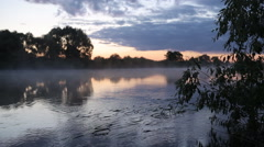 Morning sunrise reflection in misty fog rise from flowing river water. Stock Footage