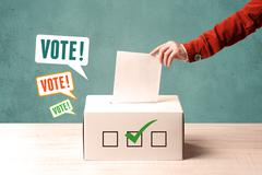 Placing a voting slip into a ballot box Stock Photos