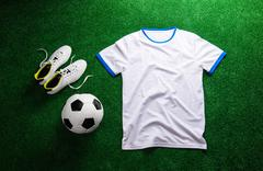 Soccer ball,cleats and white t-shirt against artificial turf Stock Photos