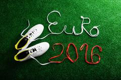 Cleats and Euro 2016 sign against artificial turf Stock Photos
