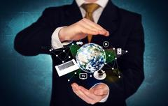Business person holding laptop and globe - stock photo