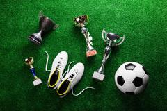 Soccer ball, cleats and trophies against green artificial turf Stock Photos