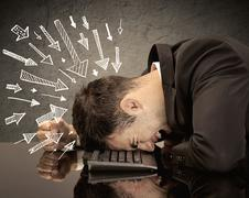 Arrows pointing at sad office worker - stock photo
