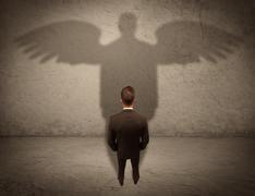 Honest salesman with angel shadow concept - stock photo