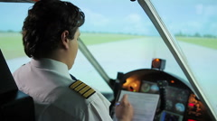 Busy aircrew commander focused on filling out flight documents in plane cockpit Stock Footage