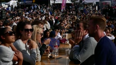 Long shot of crowd of people eating food drinking beer, beverage during a market Stock Footage