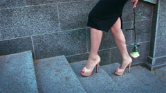 Elegant girl with slender legs with a metal rose is on the stairs Slow motion Stock Footage