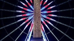Roue de Paris behind the obelisk of Louxor at night in Paris Stock Footage