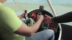 Teacher helping aviation school student control steering wheel, flight simulator Stock Footage