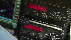 Pilot's hand turning controls on cockpit panel, connecting to radio channel Stock Footage
