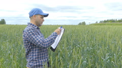 Farmer in a plaid shirt controlled his field and writing notes Stock Footage