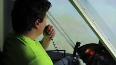 Amateur pilot talking to air traffic controller via radio in flight simulator Stock Footage