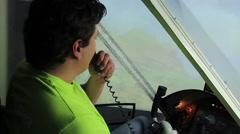 Amateur pilot talking to air traffic controller via radio in flight simulator Stock Footage