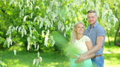 Happy pregnant woman and her husband in the park Stock Footage