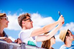 Teenagers at summer music festival in crowd taking selfie Stock Photos