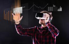 Man wearing virtual reality goggles. Studio shot, black backgrou - stock photo