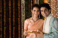 Couple holding a tray of diyas Stock Photos