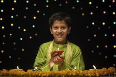 Boy holding Diya Stock Photos