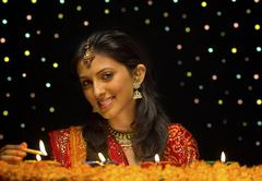 Woman lighting Diya Stock Photos