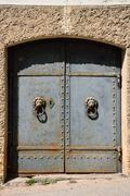 An old heavy iron door with lion motif handles. Some rust can be seen. Stock Photos