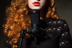 Close-up of curly-haired woman with mic - stock photo